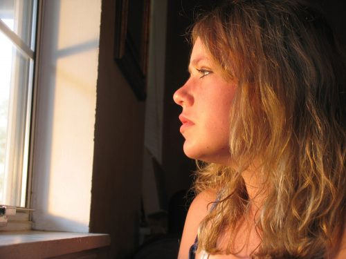 pensive young mother looks out window